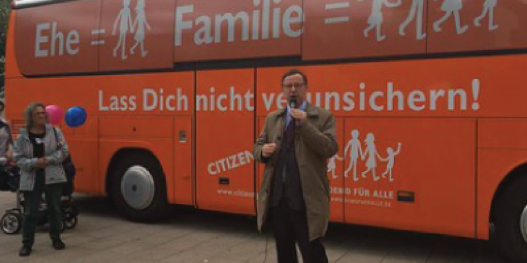 The orange bus of CitizenGo with a man speaking with a mic in front of it