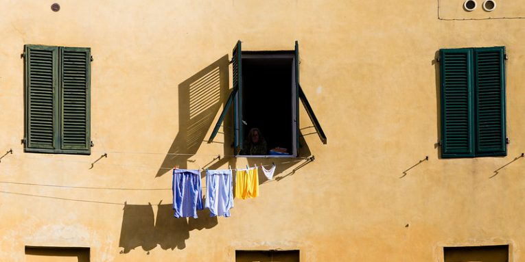 Window on a yellow wall, with clothes hanging